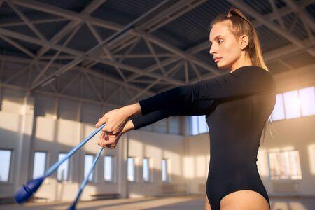 Talented female gymnast, wears black leotard, holds dark blue clubs, looks away with calm face, practicing in sports school, indoor shoot from below Standard-Bild