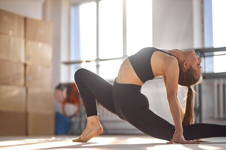 portrait of young charming gymnast bending crab, stretching body back intensively, looks up, health life style concept Standard-Bild - 132243944