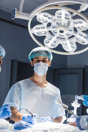 Portrait of young doctor wearing medical protective mask and scrub cap. Practicing surgeon in sterile surgical wear, bright operation room background.