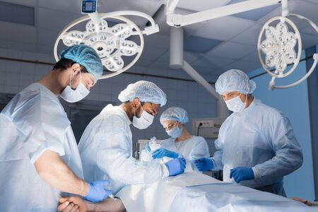 Complex surgery. Skilful surgeon works with scalpels and clamps during an operation, and his asistants taking care of blood removal from the cut Stock fotó