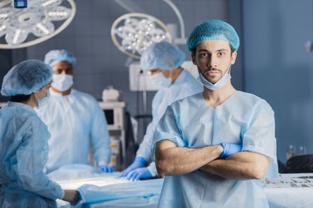 Portrait of handsome caucasian bearded young surgeon looking at camera with colleagues on background while standing in surgery with folded arms. Stock Photo