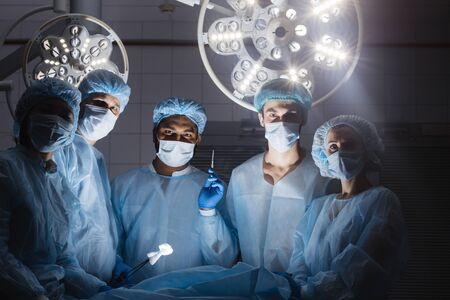 Hospital concept. Surgery team looking at camera in the operating room in a hospital clinic while operating on a patient in emergency case Stock Photo