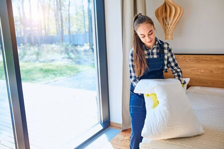 Young and careful caucasian cleaner from cleaning company set in order bed,straighten the pillow. Big panoramic window background.