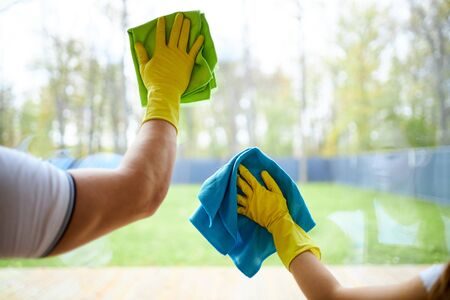 Gros plan sur des nettoyeurs tenant des chiffons, portant des gants en caoutchouc jaune. Nettoyage de vitre de fenêtre
