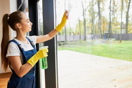 Long haired woman in uniform cleaning panoramic window with spray