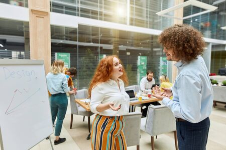 positive joyous woman with red wavy hair, passionately tells funny story, stretches palm ahead, looks aside with joyful expression, posing against working colleague in modern office