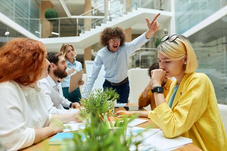 Angry severe boss yells loudly at upset young female designer, raises hand up, gestures with passion, expresses irritation. Indoor office concept