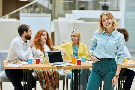 Attractive charming woman, looks at camera with engaging smile, keeps hand in pocket, poses against back ground of working colleagues sitting at table in modern designers office