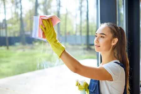 Young caucasian girl in uniform, on her hands yellow protective rubber gloves. Spraying detergent on glass and wiping window with pink rag. Cleaning service concept Stockfoto
