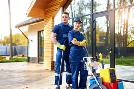 Two friends from cleaning service busy with house cleaning session, stand closely outdoors, cleaning cottage, country house. Hygiene concept.