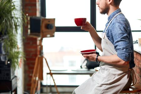 Tired professional bartender raises hand with cup of americano, holds red plate, drinks aromatic fresh prepared coffee, having rest, break time concept Banco de Imagens