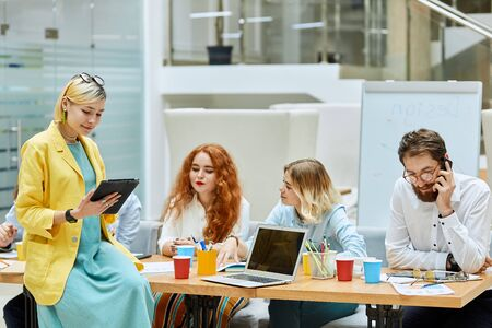 Creative talented designers working hard at table, young blonde female holds black laptop, focuses on screen, reads important information in comfortable office