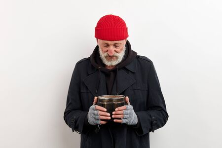 Sad old bum in black coat and red cap on head holding iron can for raising money. Isolated over white background