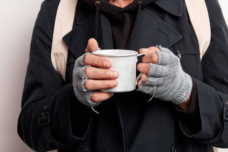 Homeless man wearing street clothes, unrecognizable. Beggar holding cup tea trying to warm up