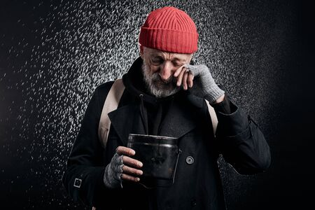 Bearded old man wearing black street clothes and holding iron cup for money, for help. Sad homeless man under heavy rain. Banco de Imagens