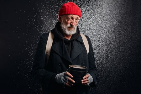 Bearded mature man seeking for help. Sad homeless man under heavy rain wait help