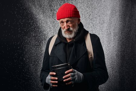 Old male wearing black street clothes and holding iron cup for money, for help. Sad homeless man under heavy rain.