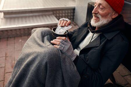 Hombre mendigo sentarse con jarra por dinero, vistiendo ropa vieja y abrigada. Vagabundo con barba gris, sombrero rojo y guantes grises Foto de archivo