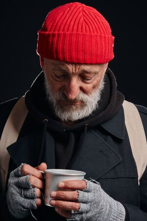 Tired and sick homeless male in coat and red hat look with sadness at mug. Portrait of bearded man isolated over black background