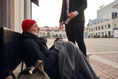 Beggar man sitting on street, businessman give dollar bill to pity beggar male