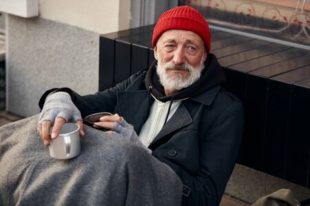 Pity poor vagrant begging in the center of city, sitting on the floor next to modern cafe. Homeless male wearing warm old clothes, red hat and wrap on legs. Stock Photo