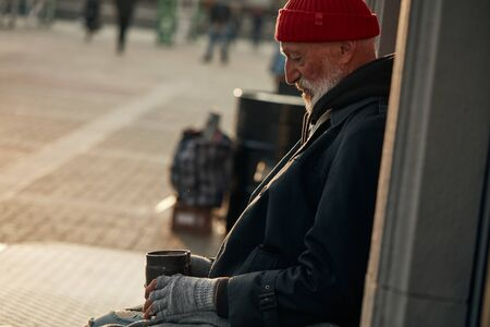 Rusted can in hands of homeless mature man in street asking for help. Poverty