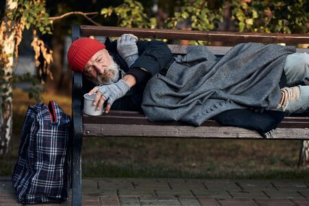 Roofless male lying on street bench asking for money, for any help. Lagguage near bench. Desperate and lonely homeless man without shelter Stock Photo