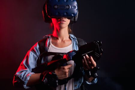Isolated shoot of young woman playing game with VR weapon, speacial mask on head. Ultra violet Stock Photo