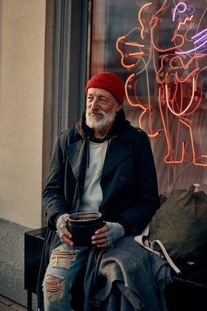 Hungry mature man with grey beard sit on street asking for help, money for shelter and food. Face full of sadness