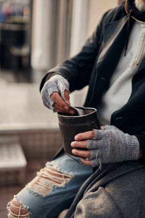 Pity hands of vagrant in grey gloves holding can for collecting money