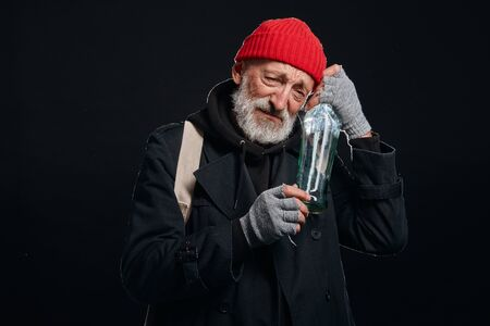 Old man with grey beard hugging empty bottle of alcohol. Male dressed in old street clothes isolated ove black background