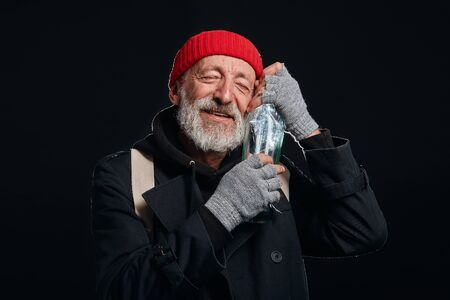 Happy old beardy man wearing red hat and black coat happily hugging bottle of drinking. Isolated over black background Imagens