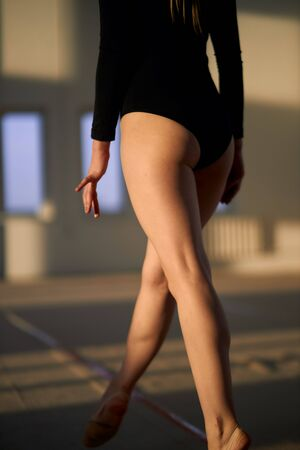 Back view of long legs of professional talented gymnast dressed in black sportswear, walking on the floor in gymnastics school, close up, blurred background