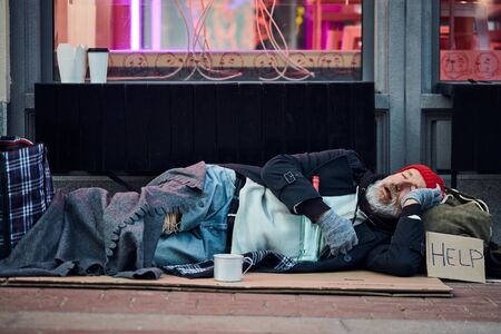Homeless needy beggar male lying on cardboard box with sign HELP, asking for help. Wearing old dirty clothes