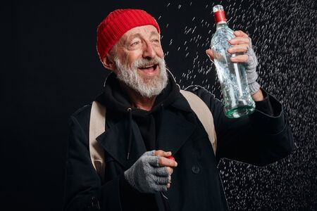 Happy old beardy man wearing red hat and black coat holding bottle of drinking. Isolated over black background