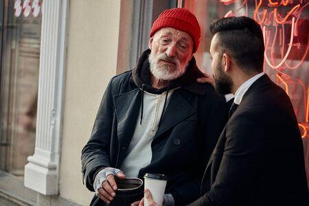 Responsive rich man sat down with homeless man in street and talk, listen to him