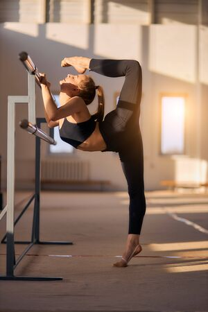 Flexible charming girl stretching out intensively using ballet bar in comfortable sportswear, performing art gymnastics element, raises leg up on tiptoe, closes eyes, in brightly lighted gym