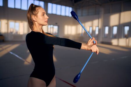 Close view of female gymnast playing with blue clubs in roomy studio, looking away, side shot, professional sport concept