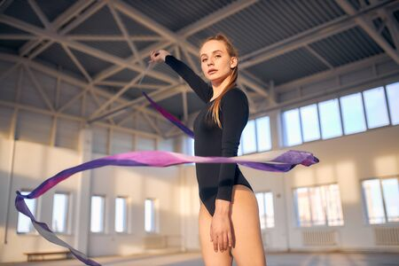 Charming beautiful art gymnast raises hand up, waving with long violet ribbon, looking straight at camera, shot from below, professional sport concept Banco de Imagens