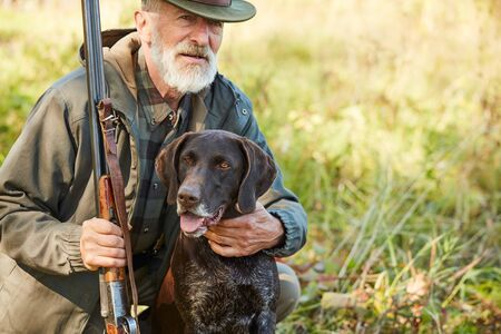 Senior man hug his hunter dog in autumn forest. Man wearing casual hunting clothes, sitting on ground.Gun in hands