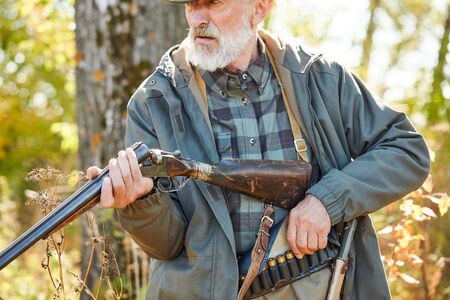 Hunter bearded male loading gun, wearing casual hunting clothes, stock and knife on lower back. Forest background