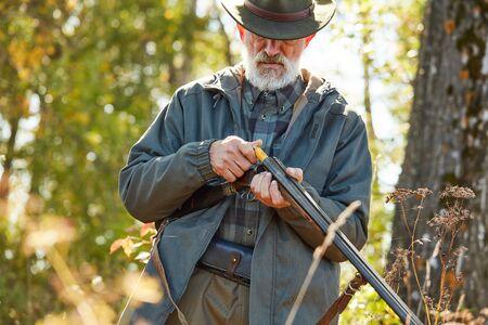 Älterer Jäger lädt Gewehr und wird schießen. Mann in der Jagd beiläufiger Kleidung, Herbstwaldhintergrund