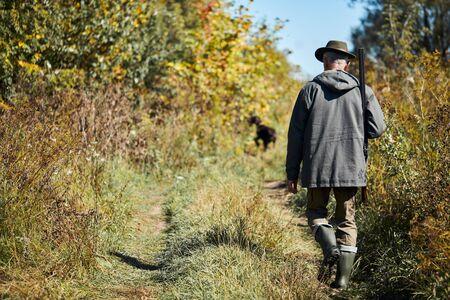 Dog seeking prey in steppe. Hunter man following labrador Reklamní fotografie