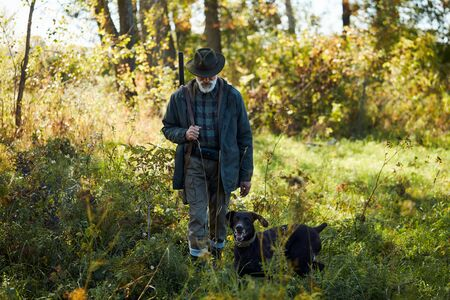 Older man with black labrador retriever with all equipment go hunting. Active hunting time