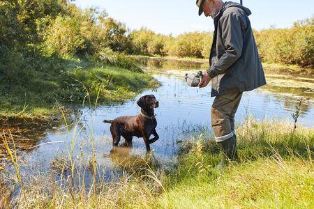 Senior cacciatore caccia alle anatre in autunno, nel lago. Il cane lo aiuta a cacciare, l'uomo tiene in mano l'anatra, il cane guarda l'anatra