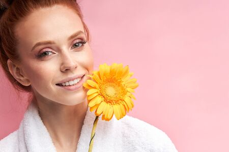 Smiling caucasian woman wearing white bathrobe, curlers on hair after shower, holding daisy flower. Natural beauty. Pink background 写真素材 - 132729500