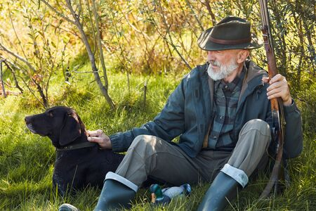 Older caucasian hunter holding his rifle, wearing cowboy hat sit on grass in autumn forest. Dog sit close looking away Stockfoto