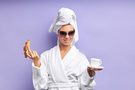 Close-up portrait of beautiful woman with cup of tea or coffee. Female dressed in bathrobe and towel on head after shower, sun glasses on eyes. Isolated violet background