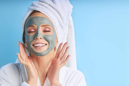 Enjoying woman with purifying mask on her face isolated on blue background