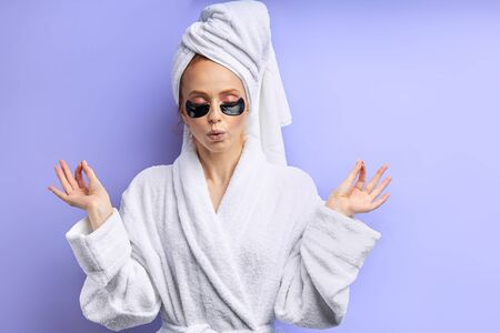 Keep calm after shower, wearing black patches under eyes. Girl in bathrobe and towel, isolated over purple background. Keep calm, skin care, careful
